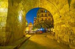 The evening streets in Cairo, Egypt. The old archway in old Cairo leads to Al-Muizz street with huge Qalawun complex of the background, Egypt stock photo