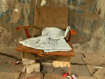 Old arm chair with bricks and old clothing royalty free stock image