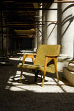 Old armchair among columns Stock Photo