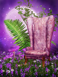 Old armchair on a meadow. Old armchair on a purple meadow with flowers and fern Royalty Free Stock Images