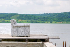 Old armchair on pier by lake Stock Image