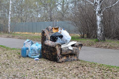 Old armchair and trash in a park Royalty Free Stock Photography