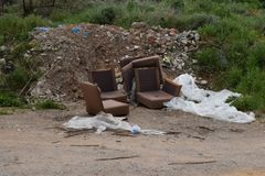Illegal waste dumping old furniture pile of rubble. Old armchairs broken furniture and pile of debris rubble and trash by the e of the road. Illegal waste stock images