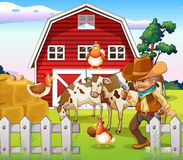 An old armed cowboy at the farm with a red barnhouse Stock Images
