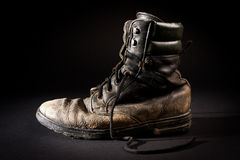 Old army boots. Old soldier's boots worn with scratches and untied shoelaces on black background Royalty Free Stock Photography
