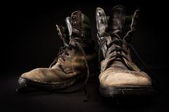 Old army boots. Old soldier's boots worn with scratches and untied shoelaces on black background Royalty Free Stock Photo