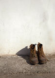 Old army shoes. On a white wall Stock Photo