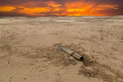 Old artillery metal projectile on the sand in the desert Royalty Free Stock Photography