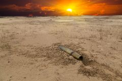 Old artillery metal projectile on the sand in the desert Stock Images