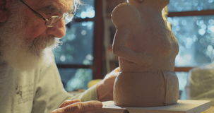 Old artist working on a clay sculpture in his studio stock footage