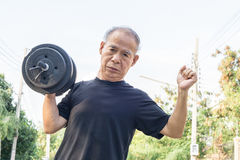 Old asia man with dumbbells. Person doing exercise outdoor. Strengthen the muscles. Your health is priceless. Hard work for a healthy lifestyle concept Royalty Free Stock Photos