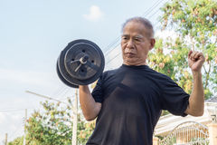 Old asia man with dumbbells. Stock Photo