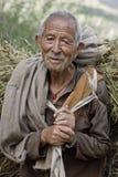 Keylong, Himachal Pradesh, India, farmer in Himalaya. Old or senior Indian farmer carrying bundle of straw or hay Royalty Free Stock Photos