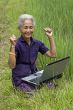 Old Asian with laptop Stock Photo
