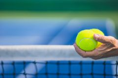 Old asian man hold two tennis balls in left hand, selective focus, blurred net and blue and green tennis court as backgroun royalty free stock images