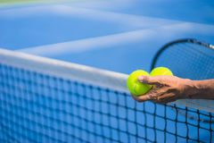Old asian man hold two tennis balls in left hand, selective focus, blurred racket, net and green tennis court as background Royalty Free Stock Images