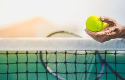 Old asian man hold two tennis balls in left hand, selective focus, blurred racket, net and green tennis court as background stock photography