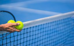 Old asian man hold two tennis balls in right hand, selective focus, blurred racket, net and blue tennis court as background stock photos