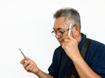 Old Asian man look at mobile phone and think something. Senior photo on white background Royalty Free Stock Photo