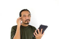 Old asian man using tablet-pc on white background Royalty Free Stock Images