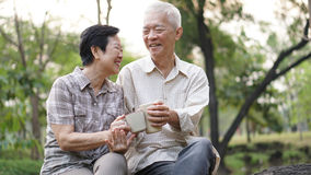 Old Asian senior couple morning date with cup of coffee in green Royalty Free Stock Images