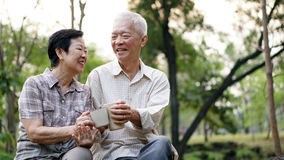 Old Asian senior couple morning date with cup of coffee in green Royalty Free Stock Photos