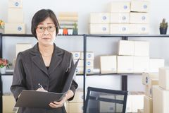 Old Asian woman check list orders stock photography