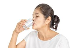 Old asian woman drinking plain of water for health. Elderly asian woman with white clothes black hair and brown eyes 60-70 years old drinking plain of water for royalty free stock photo