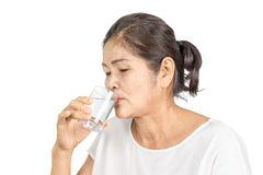 Old asian woman drinking plain of water for health. Elderly asian woman with white clothes black hair and brown eyes 60-70 years old drinking plain of water for royalty free stock image