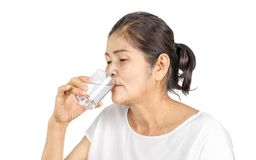 Old asian woman drinking plain of water for health. Elderly asian woman with white clothes black hair and brown eyes 60-70 years old drinking plain of water for royalty free stock images
