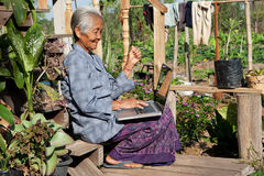 Old asian woman with laptop Royalty Free Stock Photo
