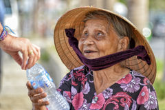 Old asian woman. Portrait of an old Vietnamese woman with wrinkles and a conical on her head who is receiving a bottle from a tourist to earn money Stock Image