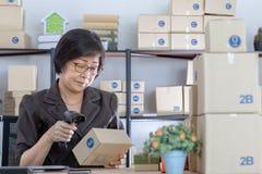 Old Asian woman using bar code machine stock photo