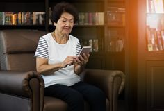 Old asian woman using smartphone.