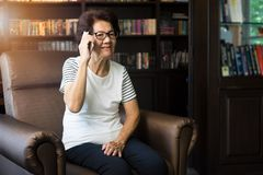 Old asian woman using smartphone for talking Stock Image