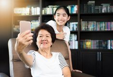 Old asian woman using smartphone for taking selfie with her gran royalty free stock image