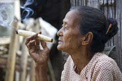 Old Asiatic woman smoking a big handmade cigar Stock Photo