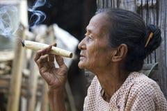 Old Asiatic woman smoking a big handmade cigar Stock Photo