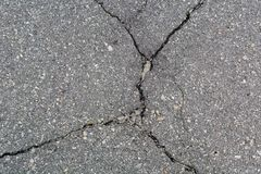 Old Asphalt covering with cracks. Gray neglected background. Royalty Free Stock Image