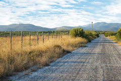 Old Asphalt Road With Mountain Background. Old Fashioned Wooden. Fence With a Rural Landscape in the Background Royalty Free Stock Images