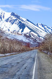 Old asphalt road in the snowy mountains. On Kamchatka Royalty Free Stock Images