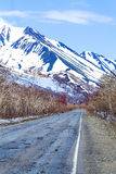 Old asphalt road in the snowy mountains. On Kamchatka Stock Images