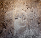 Old assyrian relief. Representing a demon holding a knife and a warrior royalty free stock photography
