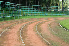 Old athletic curved track with bleacher Royalty Free Stock Photography