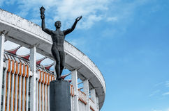 Old athletic sportsman sculpture and stadium sky Royalty Free Stock Photo