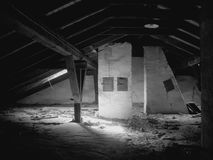 An old attic under a roof. The forgotten, light image of children's games - an attic. Black-and-white execution Stock Images