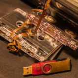 Old audio cassettes with a tangled tape, cassette tape recorder and flash drive. 80s Royalty Free Stock Photo