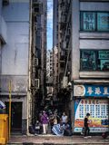 Old people gather in the shade under apartment buildings in Hong Kong. Old aunties gather in the shade of tall apartment buildings on a hot summer day in Hong stock photo