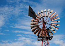 Old Australian windmill. Low angle view of old Australian windmill with blue sky and cloudscape background royalty free stock images
