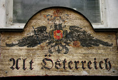 Old Austrian monarchical shop sign. An old wooden sign post depicting the bicefalous, two headed, eagle, symbol of the old Habsburg monarchy reading Alt Stock Photo